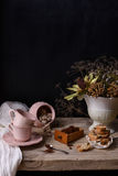 Roasted ground coffee in a wooden box with pink porcelain cups and cookies. Vintage still life on wooden table and copy space. Stock Photos