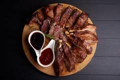 Roasted ha affettato le costole di carne di maiale del barbecue con le erbe aromatiche e due generi di souce, vista superiore fotografia stock