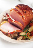 Roasted ham with vegetables. Roasted christmas ham with mushrooms and vegetables Royalty Free Stock Image