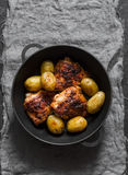 Roasted harissa chicken and new potatoes in a cast iron skillet on a dark background stock photo