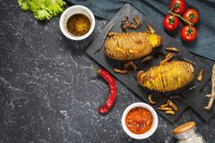 Roasted hasselback potato on dark stone background. Top view and copy space stock photos