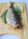 Roasted herring on a wooden Board Stock Image