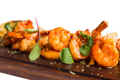 Roasted hulled shrimps with leafs on dark wooden Royalty Free Stock Photo