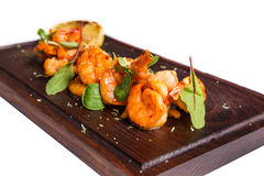 Roasted hulled shrimps with leafs on dark wooden Royalty Free Stock Image