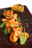 Roasted hulled shrimps with leafs on dark wooden Stock Photo