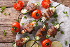 Roasted jalapeno peppers stuffed with cheese wrapped in bacon cl Stock Photos