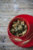 Roasted japanese turnips with leaves and seeds on red bowl Stock Photo