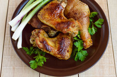 Roasted juicy chicken (legs, winglets) on a clay plate on a light wooden background Royalty Free Stock Photography
