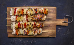 Roasted kebabs on a cutting board with sauce wooden rustic background top view close up Royalty Free Stock Photography