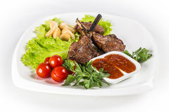 Roasted lamb chops with tomatos. Roasted lamb chops on white plate Royalty Free Stock Photography