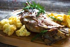 Roasted lamb leg. On wooden background royalty free stock images
