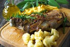 Roasted lamb leg. On wooden background stock images