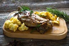 Roasted lamb leg. On wooden background stock photography