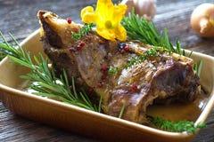 Roasted lamb leg. On wooden background royalty free stock photography