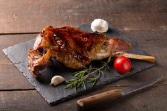Roasted lamb leg. On wooden table stock photo