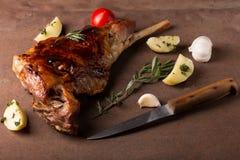 Roasted lamb leg. On wooden table stock image