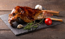 Roasted lamb leg. On wooden table stock photography