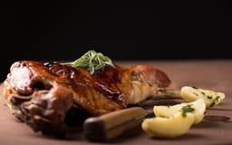 Roasted lamb leg. On wooden table royalty free stock photos