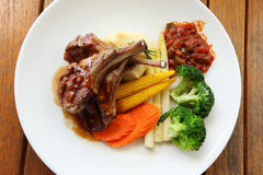 Roasted lamb with tomato sauce and fresh vegetables Stock Images