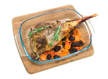 Roasted leg of lamb with prunes and carrots on a white backgroun Royalty Free Stock Photos
