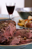 Roasted Leg Of Lamb with vegetables. And red wine in the background Stock Photography