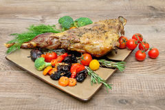 Roasted leg of lamb with vegetables, greens and prunes on a plat Stock Image