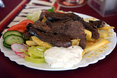 Roasted liver with portion of french fries on a plate. Roasted liver with portion of french fries and vegetables on a plate stock images