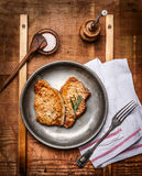 Roasted marinated pork steaks  served on rustic kitchen table Royalty Free Stock Image