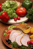 Roasted meat. Traditional food setting with roasted meat with fruits and vegetables on wooden table stock images