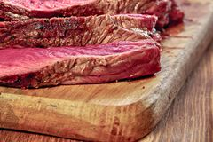 Fried meat with blood. Sliced pieces of a well-made juicy steak close-up. Wooden background. Rustic stile. Selective focus. stock photography