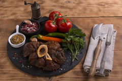 Roasted meat on the bone Osso Buco on board Royalty Free Stock Photography