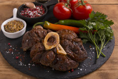 Roasted meat on the bone Osso Buco on board Stock Images