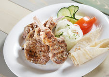 Roasted meat on the bone with vegetables stock photography