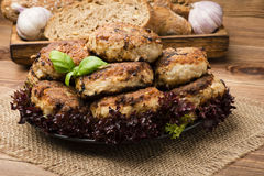 Roasted meat cutlets on the plate on the wooden surface. Royalty Free Stock Photography