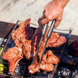 Roasted meat on the grill with male hand. Stock Photography