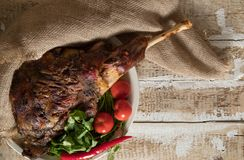 Roasted meat leg of lamb baked whole lies with fresh tomato greens and hot pepper on a platter. On an old wooden surface Royalty Free Stock Photos