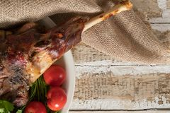 Roasted meat leg of lamb baked whole lies with fresh tomato greens and hot pepper on a platter. On an old wooden surface Stock Photography