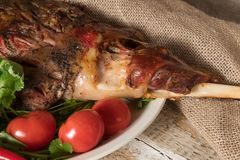 Roasted meat leg of lamb baked whole lies with fresh tomato greens and hot pepper on a platter royalty free stock images