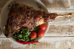 Roasted meat leg of lamb baked whole lies with fresh tomato greens and hot pepper on a platter. On an old wooden surface Stock Photo