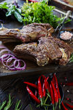 Roasted meat with onions, garlic, spices, fresh herbs, red pepper and salt. On wooden cutting board in rustic style. selective focus, prime beef, slow food royalty free stock image