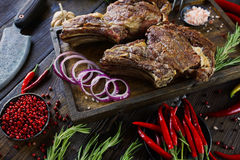 Roasted meat with onions, garlic, spices, fresh herbs, red pepper and salt. On wooden cutting board in rustic style. selective focus, prime beef, slow food stock images