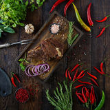 Roasted meat with onions, garlic, spices, fresh herbs, red pepper and salt. On wooden cutting board in rustic style. top view, prime beef, slow food concept royalty free stock images