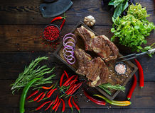 Roasted meat with onions, garlic, spices, fresh herbs, red pepper and salt. On wooden cutting board in rustic style. top view prime beef, slow food concept royalty free stock photography