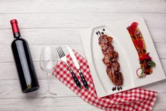 Roasted meat with pineapple, wine bottle in balsamic sauce on a white wooden board stock image