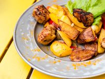 Roasted meat with potatoes, ojaxuri, hot in Georgian on a wooden table. Top view stock photos