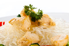 Roasted meat, rice noodles and vegetables on white Stock Image
