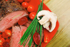 Roasted meat served on red dish Stock Photography