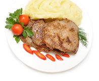 Roasted meat with vegetables on white plate stock images