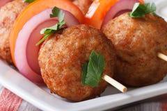 Roasted meatballs on skewers on a plate macro. Horizontal Stock Image