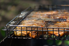 Roasted meet during cooking on the mesh. In open fire Royalty Free Stock Images